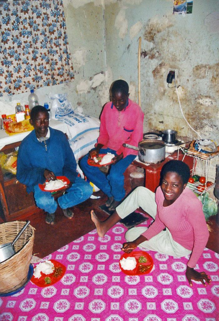 2001, Musole, Kabwe, Zambia, drie jongeren eten op de grond